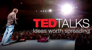 TED Talk speaker on stage with TED Talks logo